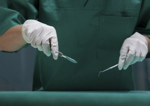 Surgeon in green uniform holding surgical tools.