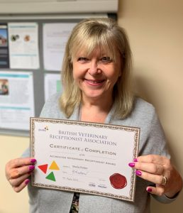 Image shows vet receptionist Sheila Potter holding her gold certificate from the BVRA